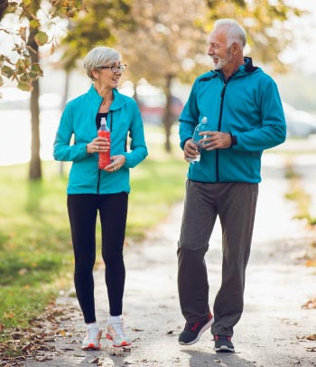 55+ couple walking together with water bottles