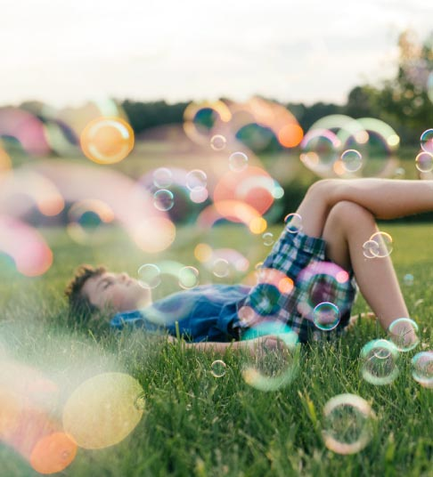 A boy playing in bubbles on a warm summer day