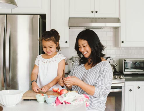 Mom And Daughter Making A Snack Together In Kitchen