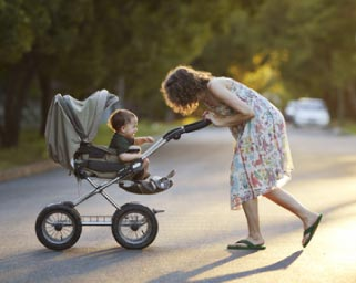 Mother & son walking with stroller in the sunset
